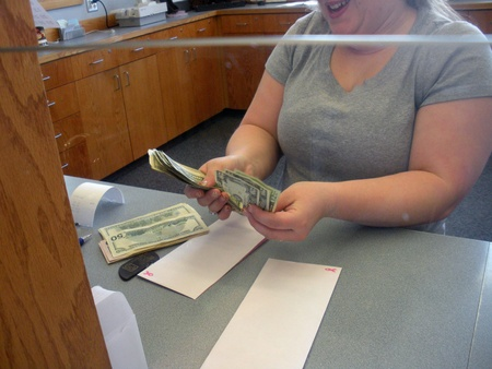 LEWISTONIDAHOUSA _Female  Cashier countting US Dolloar notes bill at Potlatch Federal Credit Union bank 14 March 2011