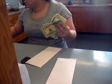 credit union: LEWISTONIDAHOUSA _Female  Cashier countting US Dolloar notes bill at Potlatch Federal Credit Union bank 14 March 2011