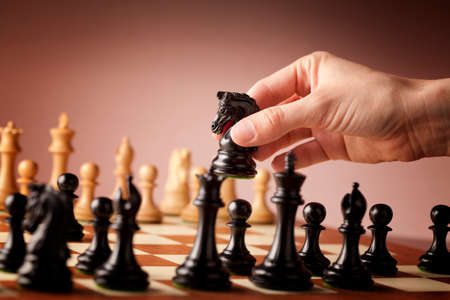 rycerz: Mężczyzna strony przesuwając czarny rycerz szachy podczas gry w szachy Zdjęcie Seryjne