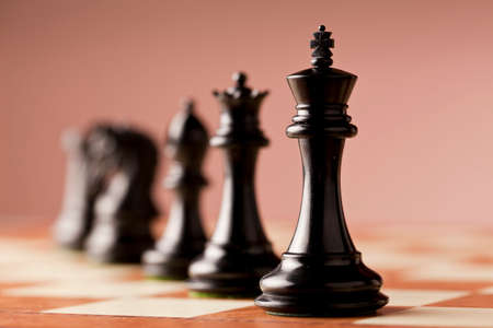 burl wood: A line of luxurious black Staunton chess pieces carved in genuine ebony wood standing on elm burl and birds eye maple superior traditional chessboard Stock Photo