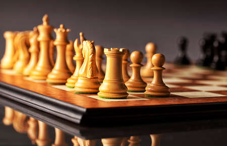 facing right: Chess opening - initial phase of a chess game - right flank of white army in focus facing blurred black pieces Stock Photo