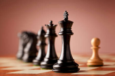 A line of luxurious chess pieces carved in genuine ebony wood facing a single white pawn made of natural boxwood standing on elm burl and birds eye maple superior traditional chessboard