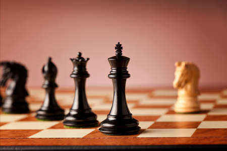 overwhelming: Overwhelming advantage - main black chess pieces facing single white knight on a luxurious traditional chessboard Stock Photo