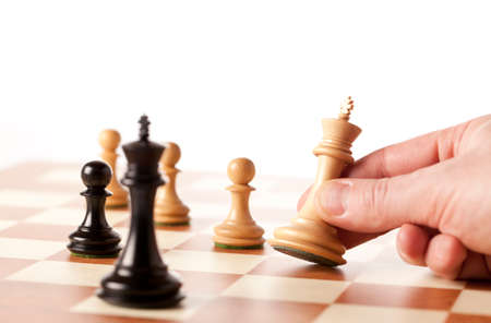 playing chess: Playing chess - hand moving white king Stock Photo