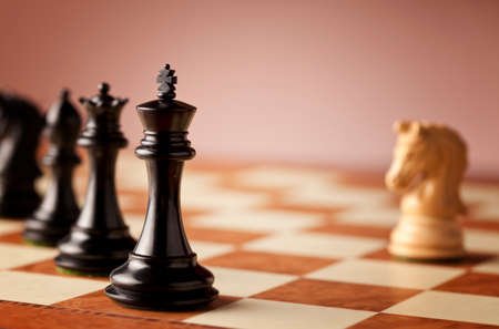 overwhelming: Overwhelming advantage - main black chess pieces facing single white knight on a luxurious traditional chessboard in focus Stock Photo
