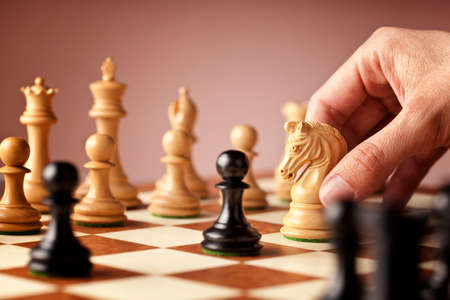 chess move: Male hand moving the white chess knight in the middle of a chess game attacking the blacks Stock Photo