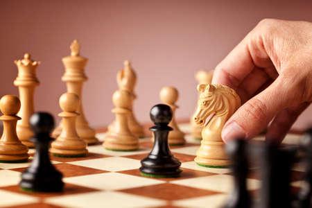 ajedrez: Mano masculina mover el caballo de ajedrez blanco en medio de un juego de ajedrez atacar a los negros