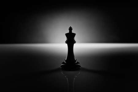 challenges: Solitary black chess king carved in genuine ebony wood in focus standing on a glossy table in the dark