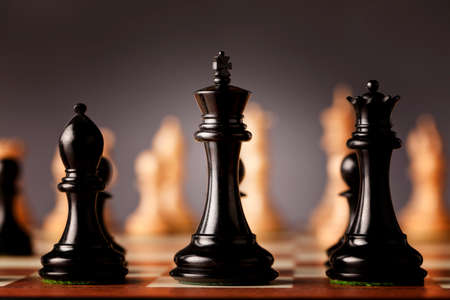 ebony wood: A line of luxurious black Staunton chess pieces carved in genuine ebony wood in focus standing traditional wooden chessboard facing the army of white pieces before the battle