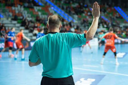 Handball referee gives signal playing for time during handball match.