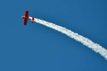 Red plane on the blue sky during air show