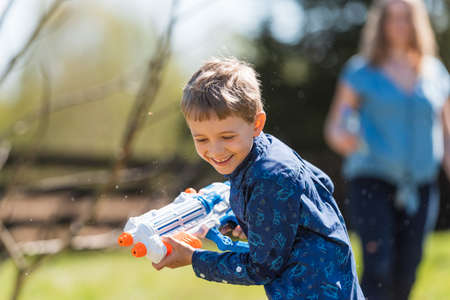 The boy with water gun runs away from hie mother. Water splashes are an Easter tradition in Poland Stok Fotoğraf