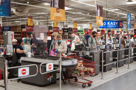 WROCLAW, POLAND - MAY 22, 2020. Customers in front of the checkout in Carrefour supermarket. Due to coronavirus pandemic people have face masks.