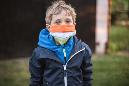 Young boy with face mask due to pandemic Covid-19.