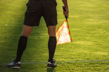 Soccer touchline referee - detail of legs and hand with the flag.