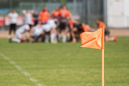 Flag on the pitch with rugby match in the background.