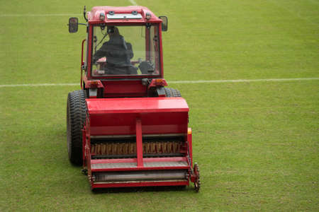 A man in a tractor with a disc seeder drill sowing grass on a football field