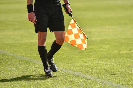 Legs and flag of assistant football referee