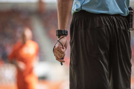Hand of soccer referee with wristwatch and whistle.