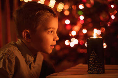 Seven year old boy with candle and Christams tree in the background