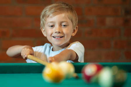 5-6 years old boy playing billiards