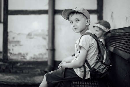 Boy and girl waiting on the bench for a train during warm summer day