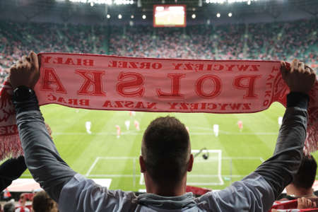 A white and red scarf with the word Poland (in Polish) held by a fan during a football match.