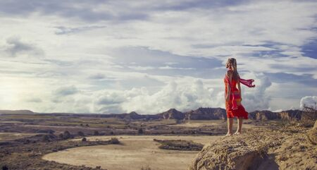 Panoramic view of a pretty young girl in a red and orange dress and a scarf in the wind, standing looking at the horizon in dry Monegros desert landscape with mountains in the background and a blue sky with clouds. Stock Photo