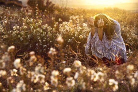 A bent down young girl with long blond hair and her hands looking up in a woolen grey poncho on a field with white flowers during sunset, with the sun on her back.