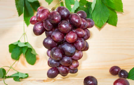 grapes on a brown background. a bunch of grapes. grapes, green leaves. dark blue grapes. juice in a glass Фото со стока