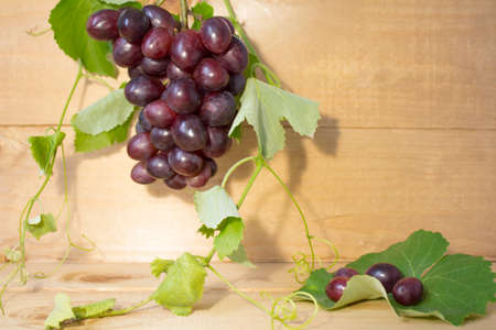 grapes on a brown background. a bunch of grapes. grapes, green leaves. dark blue grapes. juice in a glass Banco de Imagens