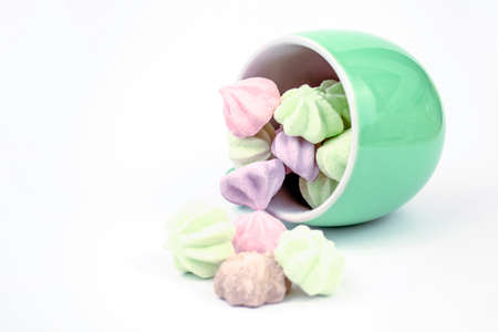 Meringue on a white background. Multi-colored meringues in a green cup on a white background. background