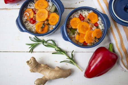Soup, Vegetable soup, blue pan. Hot soup vegetable soup, carrot on a white background. Rosemary branch. Pepper, Ginger. Two pots. view from above, place for text Stok Fotoğraf