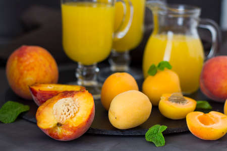Summer apricot juice. Fresh peach juice. Peaches and apricots with a green leaf on a dark surface. copyspace