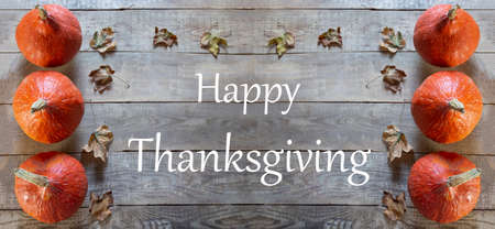 Happy Thanksgiving Day. Pumpkins and leaves on a wooden background. Happy Thanksgiving lettering. Banner