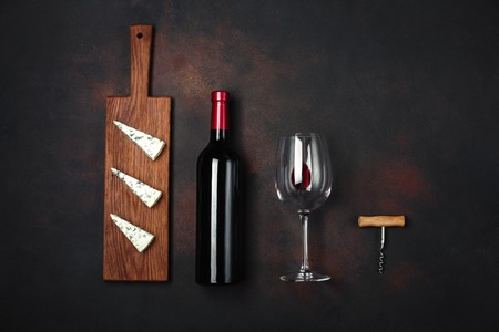 Bottle of wine, blue stinky cheese, corkscrew and wineglass on rusty background, up wiev