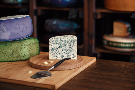 Cheese heads with slices and knives lie on a wooden board with an interior 스톡 콘텐츠