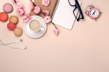 White cup with cappuccino, sakura flowers, macarons, alarm clock, notebook on a pastel pink background.