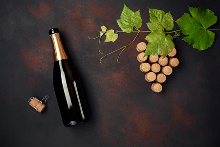 Bottle of champagne, grape bunch of cork with leaves on rusty background