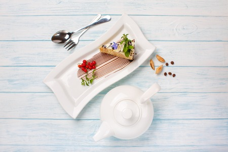 piece of cake, tea in a teapot on blue boards, top view