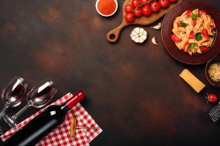 Pasta with cheese, cherry tomato sauce, wineglass and bottle wine, garlic, turmeric on rusty background