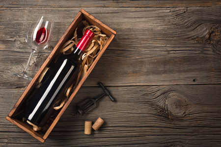 Red wine in a box with a glass and a corkscrew on a wooden table 스톡 콘텐츠