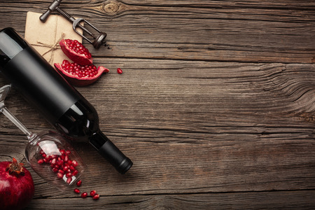 Ripe pomegranate fruit with a glass of wine, a bottle and a corkscrew on a wooden background. Top view with copy space.