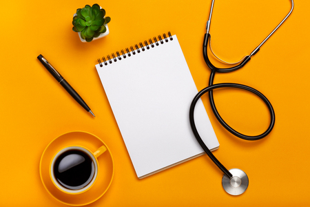 Top view of a doctor's table with notepad and pen stethoscope, keyboard, prescription and pills, a cup of coffee on a yellow background with space for your text.