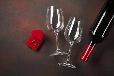 Valentines Day with a bottle of wine and a glass and an engagement ring. Top view with copy space