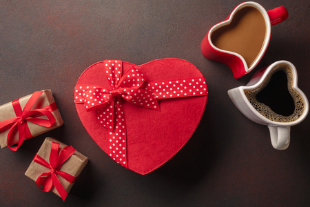 Valentine's Day with gifts, a heart-shaped box, cups of coffee, heart-shaped cookies and a blackboard. Top view with copy space