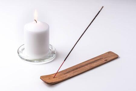 Kerze und Räucherstäbchen auf einem Holzteller mit weißem Hintergrund Standard-Bild