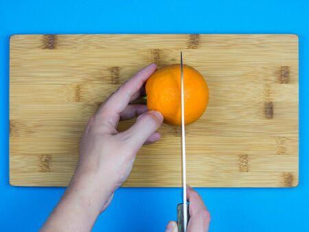 Hombre caucásico con un cuchillo para cortar una naranja en la parte superior de una superficie de madera con fondo azul.