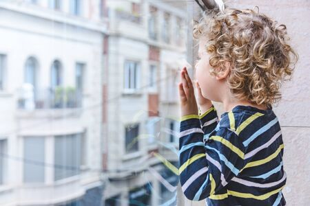 blonde little girl looks at the street from the balcony during COVID-19 confinement