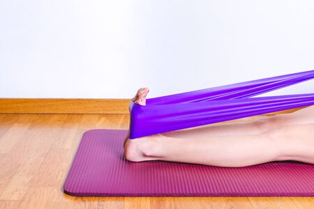 detail of caucasian woman stretching calves with a purple gym elastic band